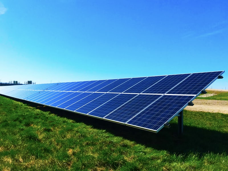 A bright green field with solar panels and a blue sky