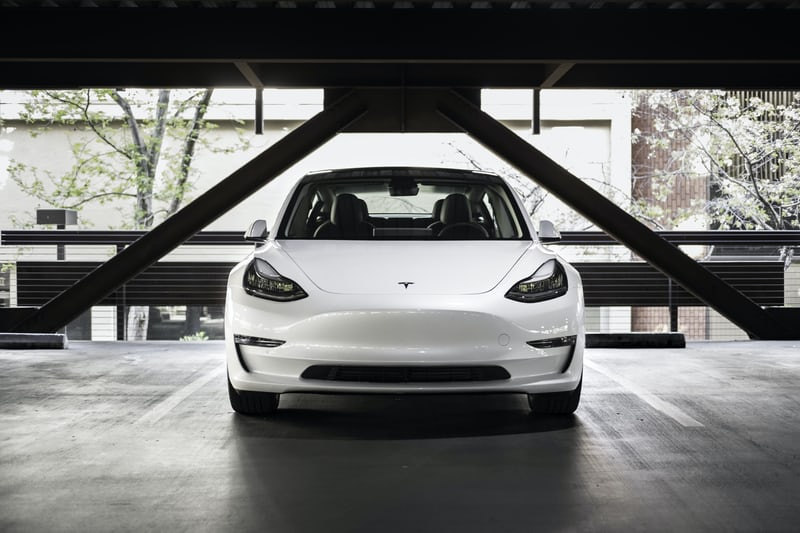Clean white Tesla Model 3 in a parking from the front angle